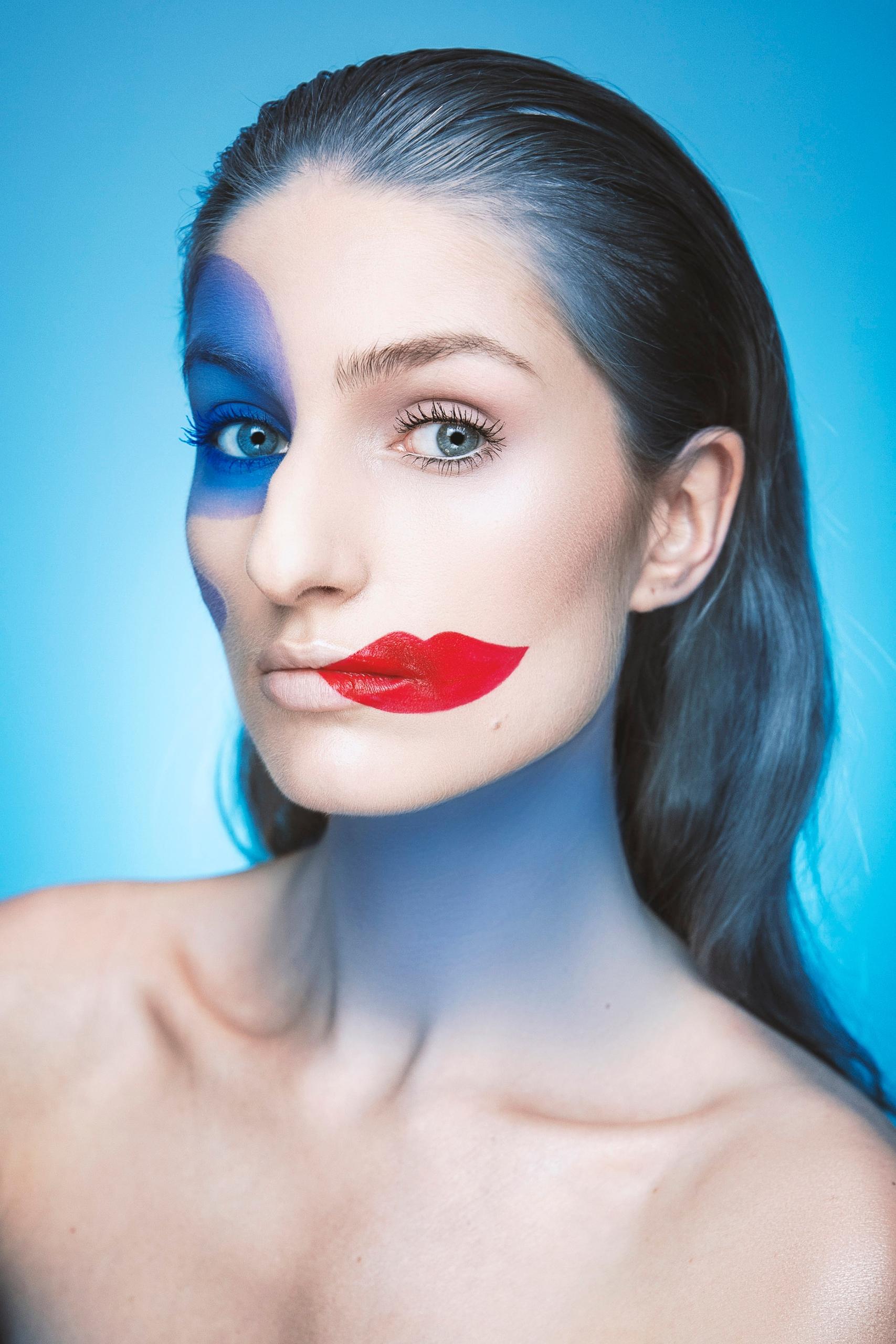 Fotografia przedstawia kobietę na niebieskim tle. Kobieta ma namalowane czerwone usta z boku twarzy.