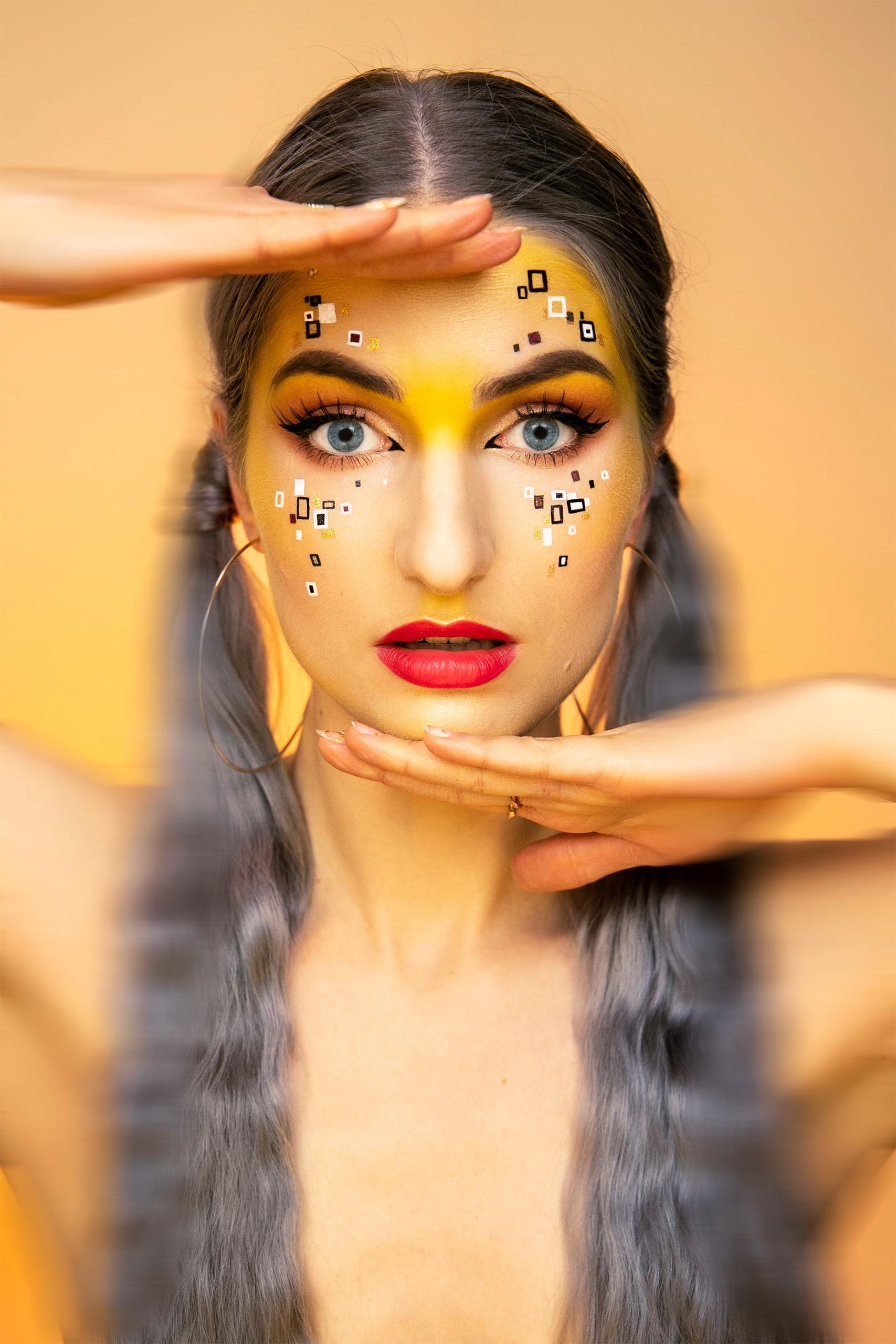 Fotografia przedstawia portret kobiety w mocnym makijażu. Całość w ciepłej, żółtej tonacji.