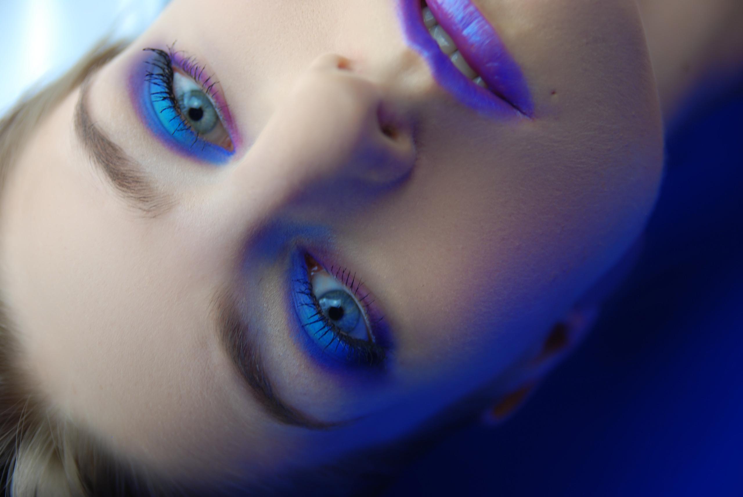 Zdjęcie przedstawia twarz młodej kobiety w makijażu, do góry nogami, z niebieskim światłem padającym na prawą część twarzy.