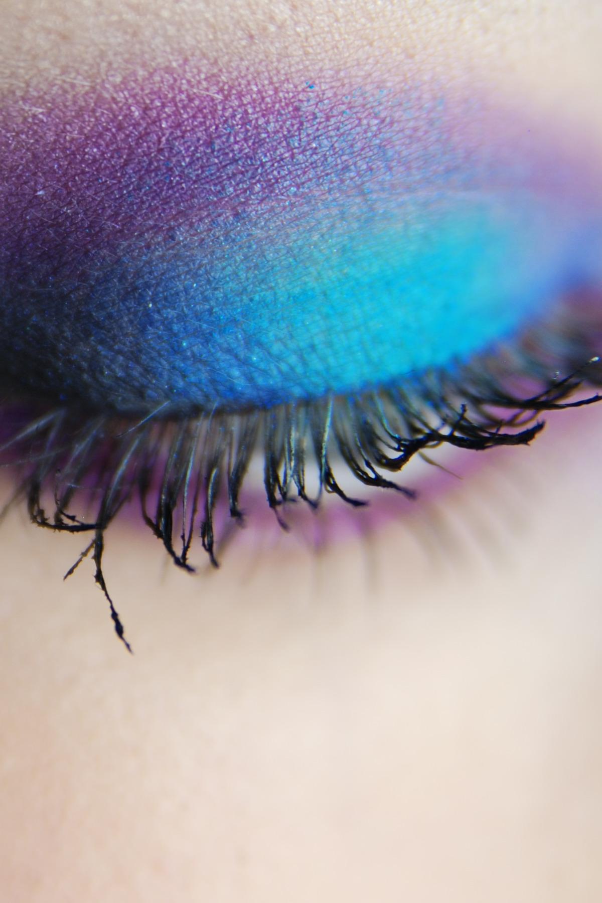 Zdjęcie przedstawia zbliżenie na rzęsy powieki oka pomalowanej na niebiesko-fioletowo.