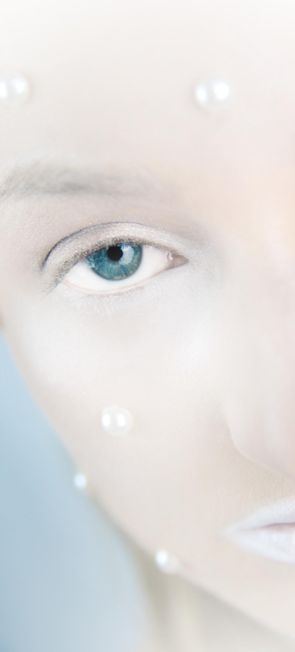 Zdjęcie przedstawia połowę twarzy kobiety, do której przyczepione są perły, a powieka oka pomalowana jest na biało.