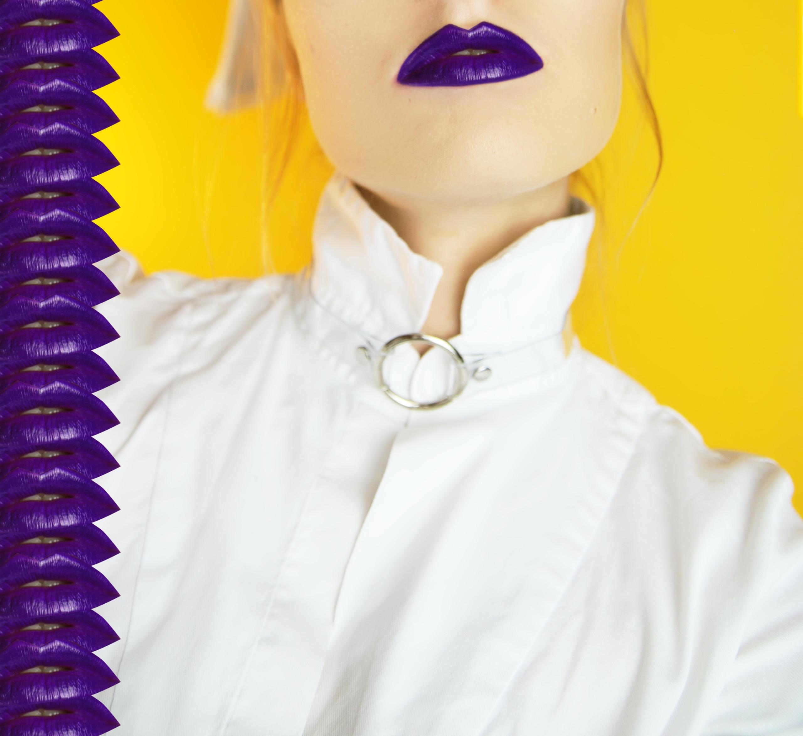 Zdjęcie przedstawia zbliżenie na popiersie kobiety z fioletowymi ustami. Kobieta ma białą koszulę i ozdobę na szyi, widzimy żółte tło, a z lewej strony wzór złożony z ust.