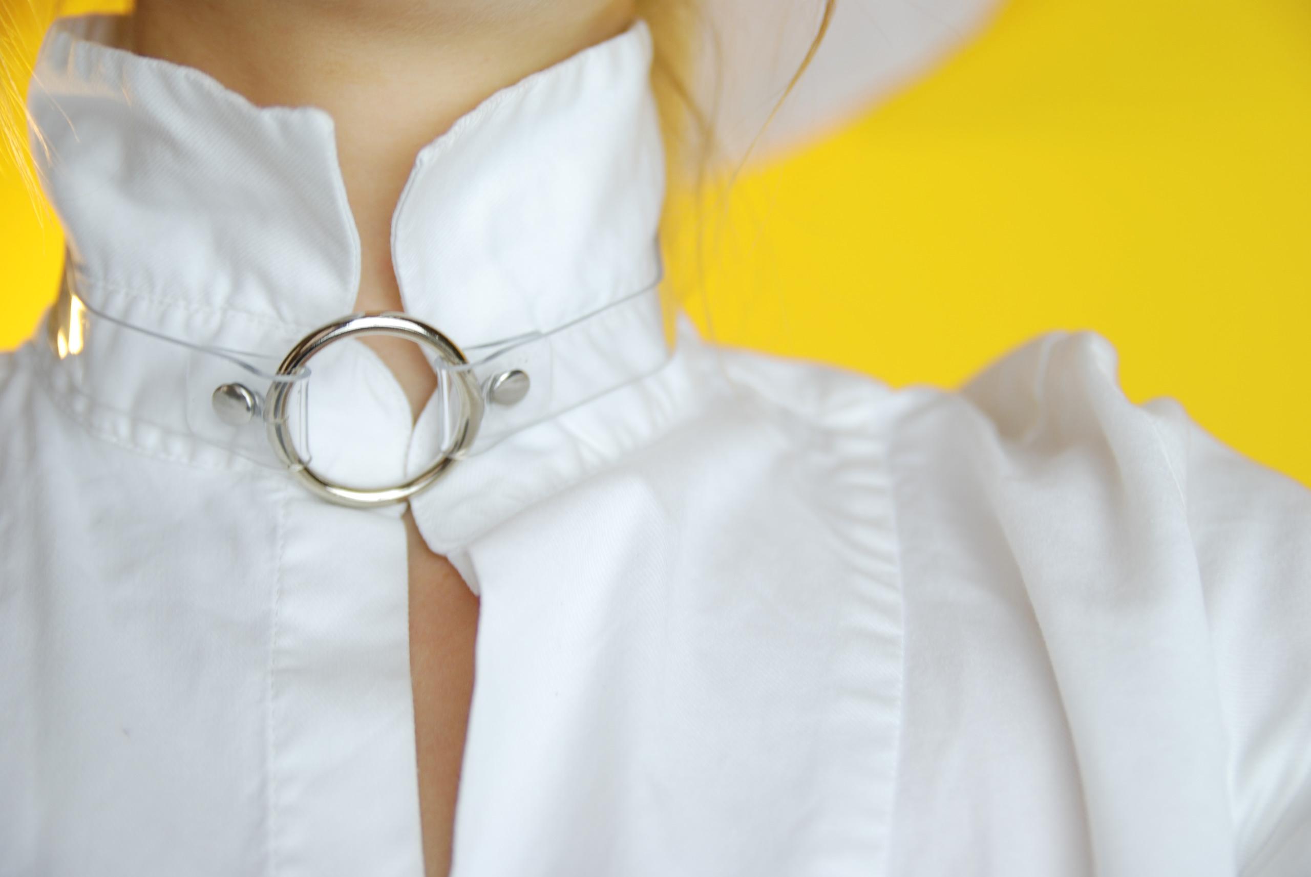Zdjęcie przedstawia zbliżenie na szyję człowiek ubranego w białą koszulę, z tyłu widać żółte tło.