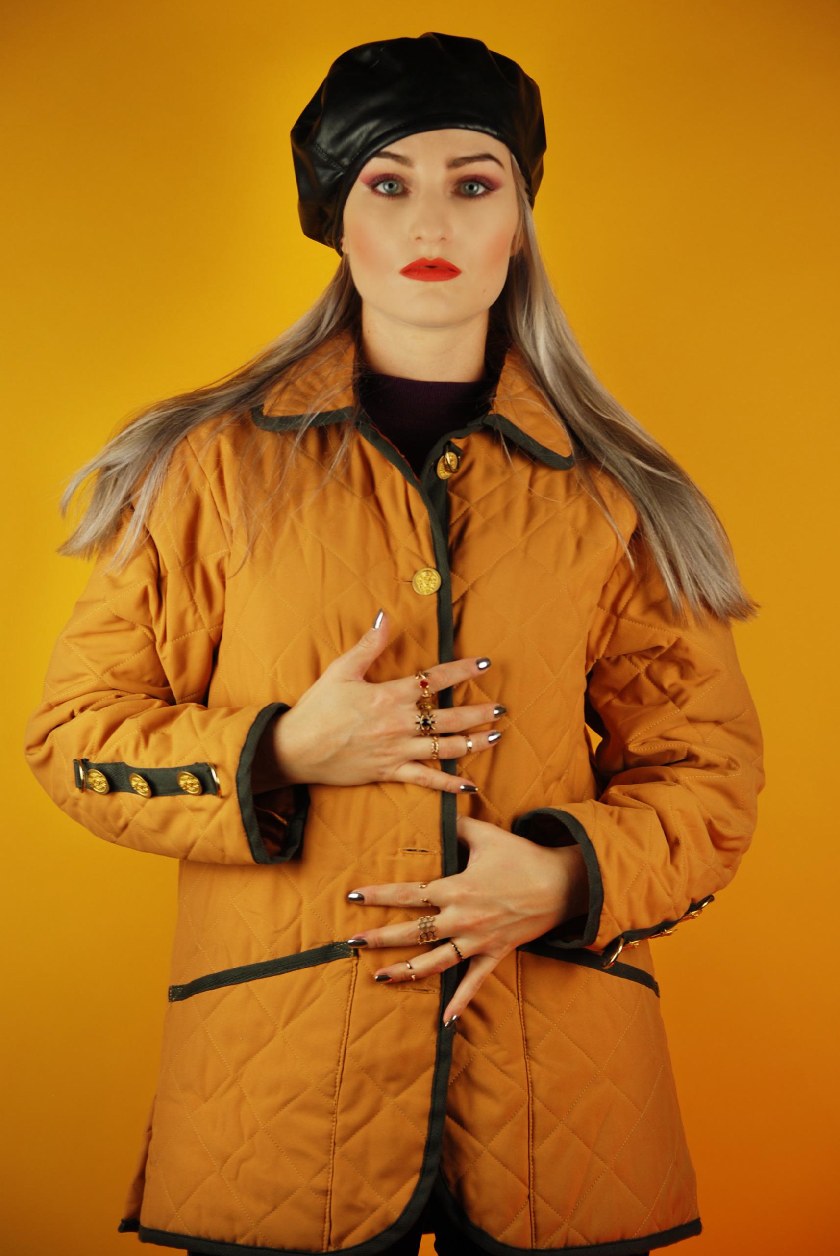 Zdjęcie przedstawia młodą kobietę ubraną w żółtą pikowaną kurtkę, kobieta ma czarny beret na głowie, pomarańczowe usta, całość na żółtym tle.