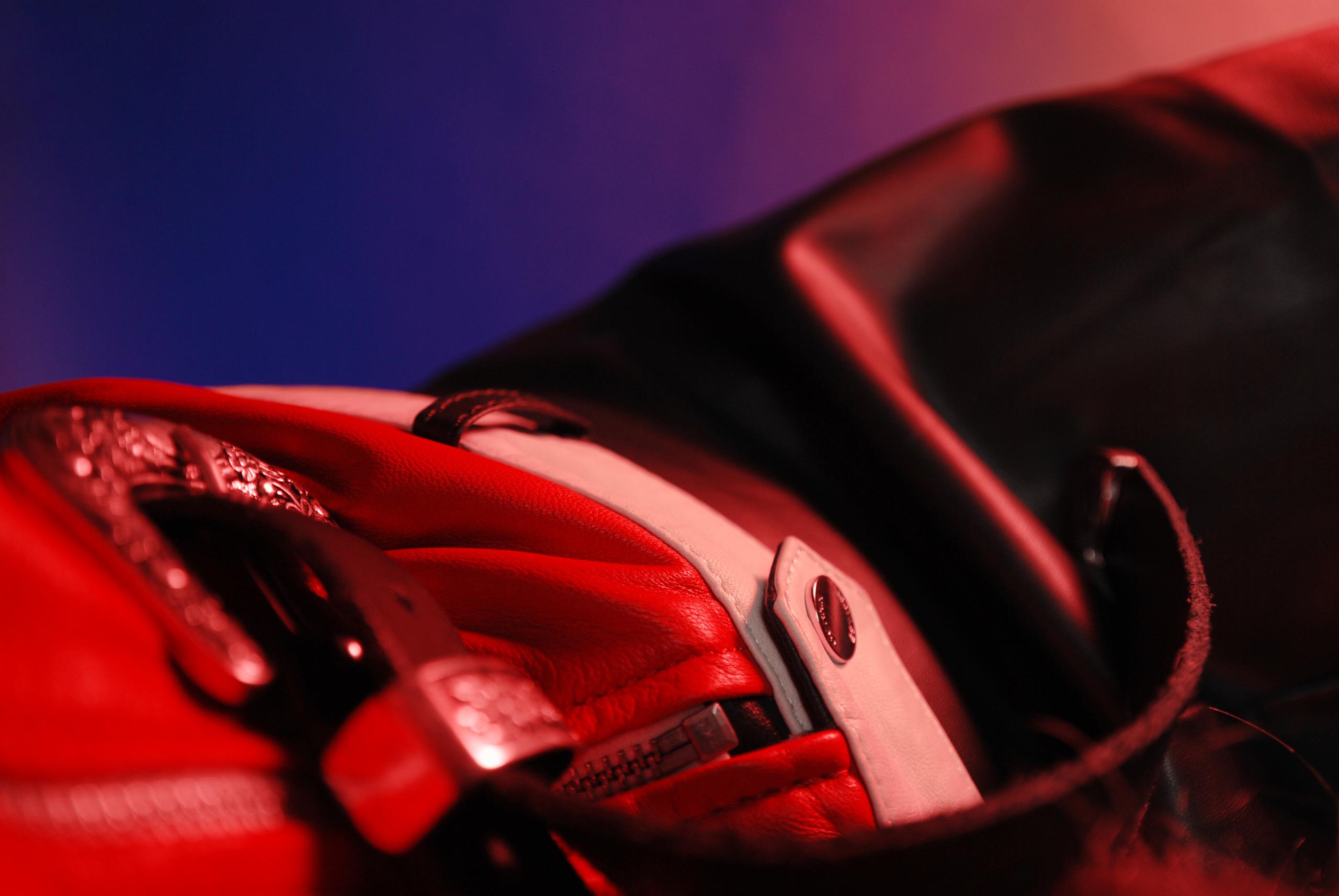 Zdjęcie przedstawia zbliżenie na fragment ubioru, widać pasek z metalową klamrą i czerwoną kurtkę.