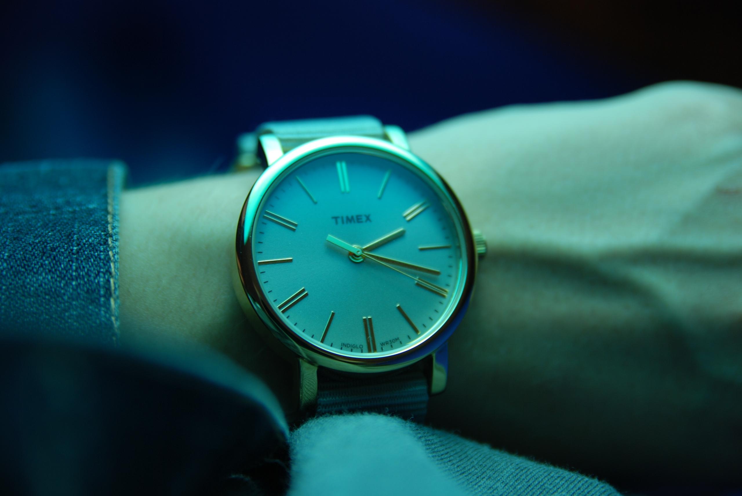 Zdjęcie przedstawia zbliżenie na zegarek, scena oświetlona chłodnym światłem.