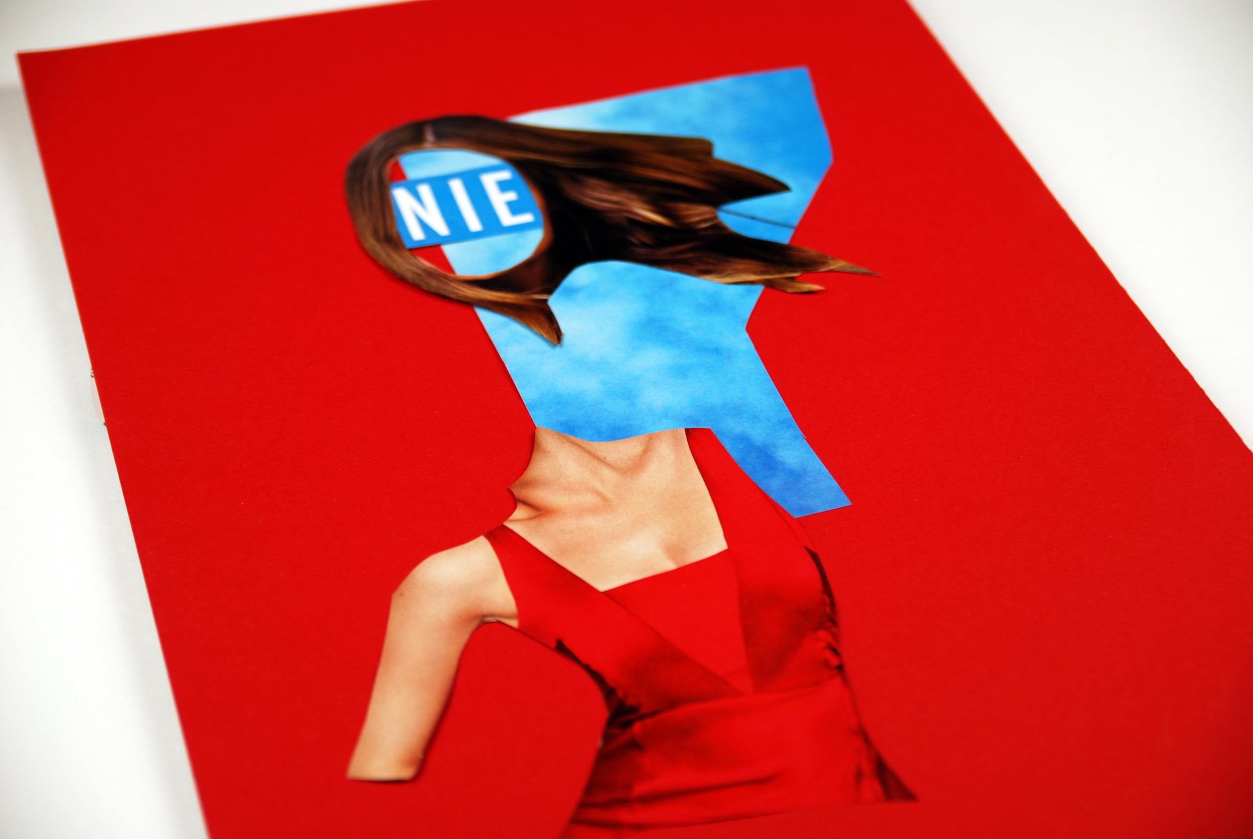 Zdjęcie przedstawia czerwony karton, na którym leżą elementy powycinane z gazet, tworząc kolaż.