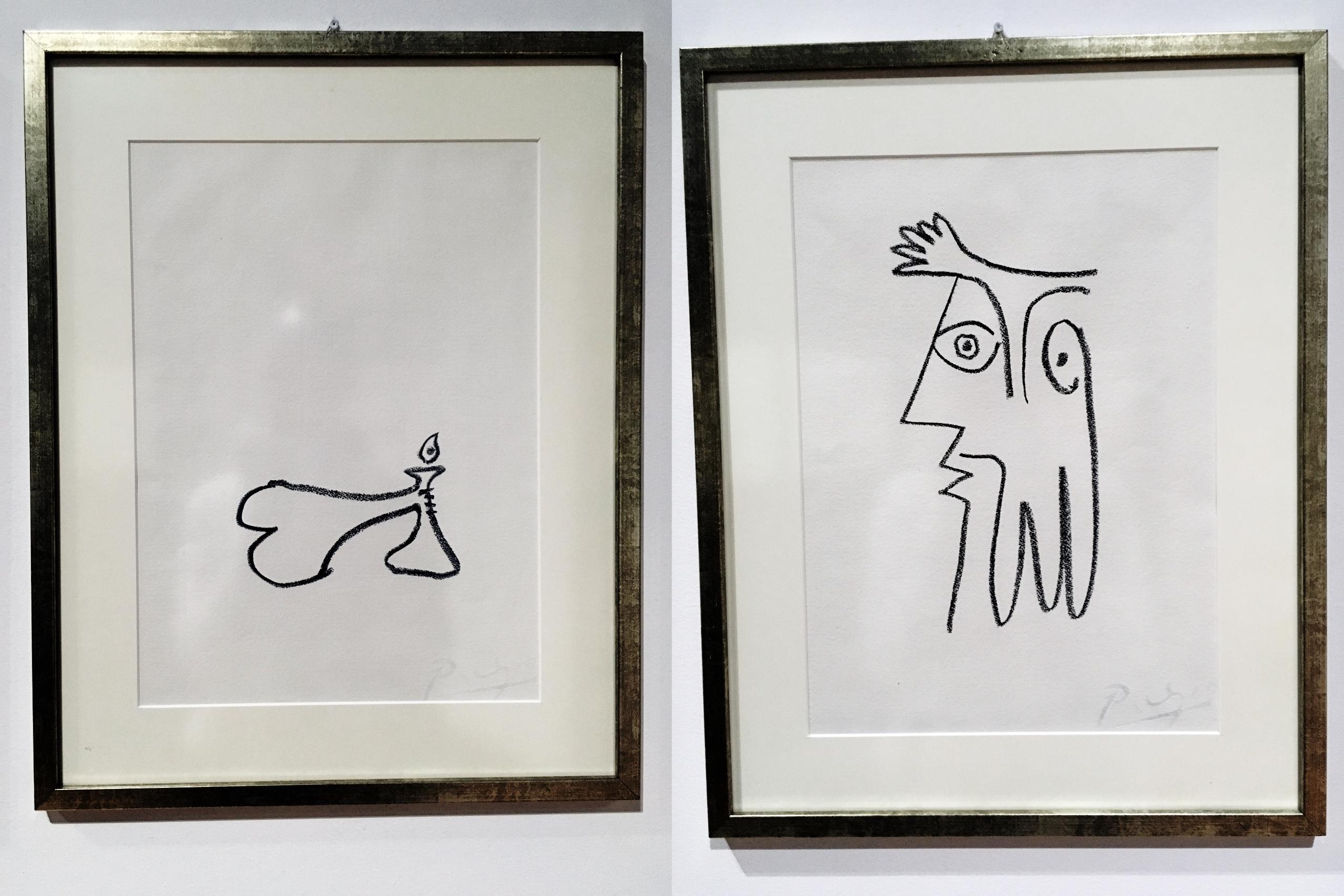 Zdjęcie przedstawia dwa rysunki znanego artysty Pabla Picassa. Rysunki są oprawione w ramki i mają charakter abstrakcyjny.