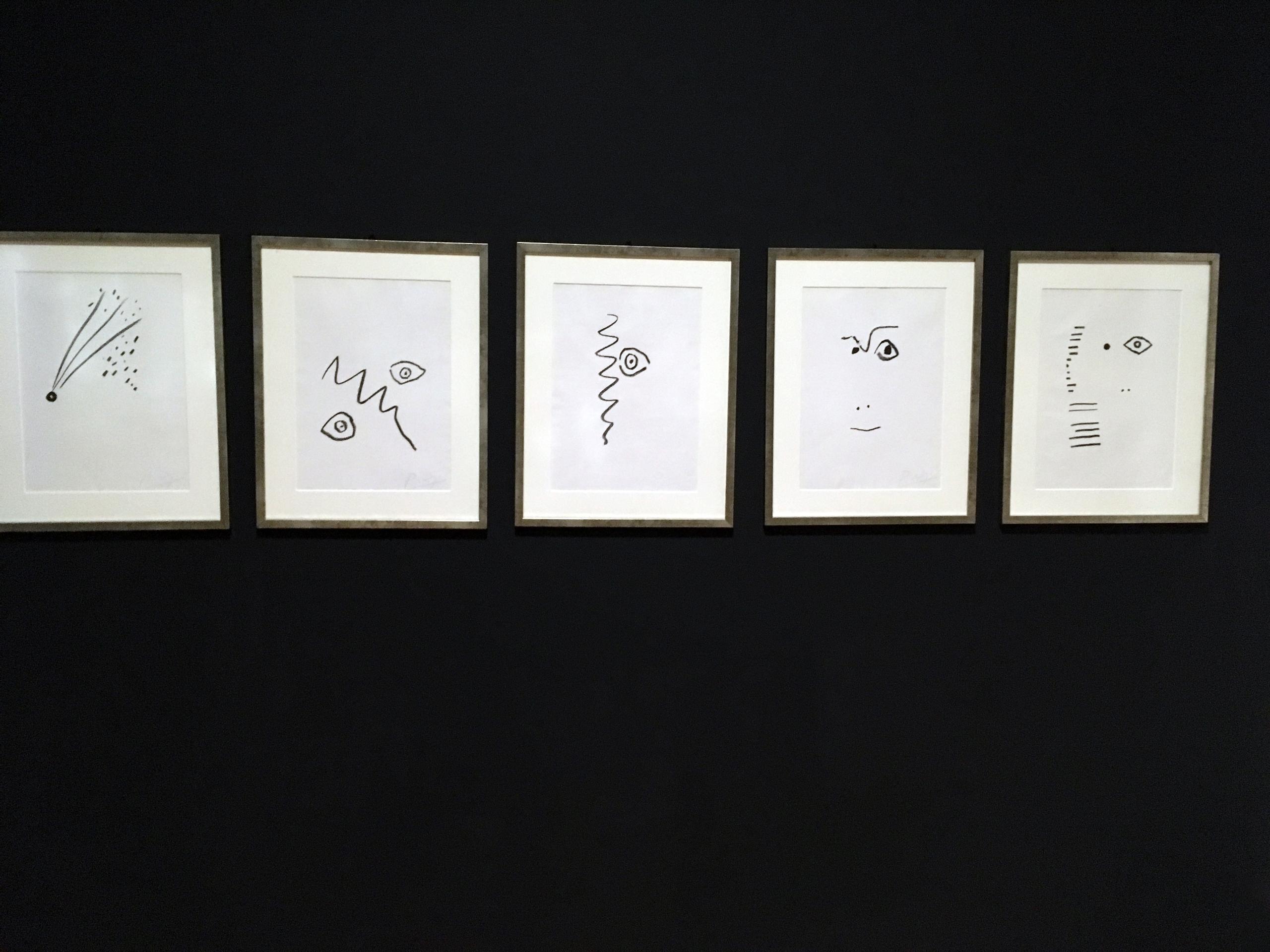 Zdjęcie przedstawia serię pięciu prac znanego artysty Pabla Picassa zawieszonych na czarnej ścianie. Prace przedstawiają proste formy.
