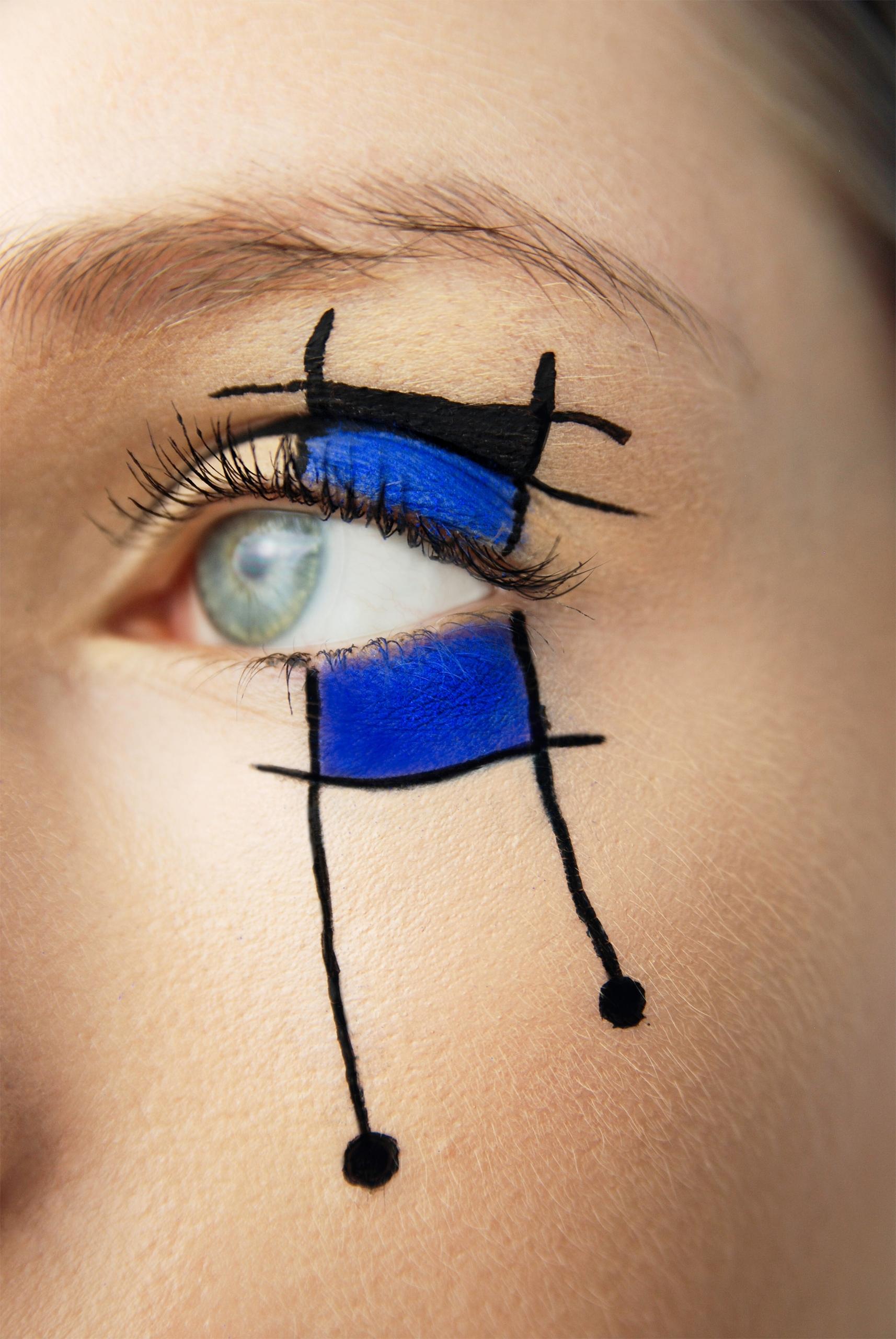 Zdjęcie przedstawia zbliżenie na oko pomalowane w geometryczne czarno-niebieskie kształty.
