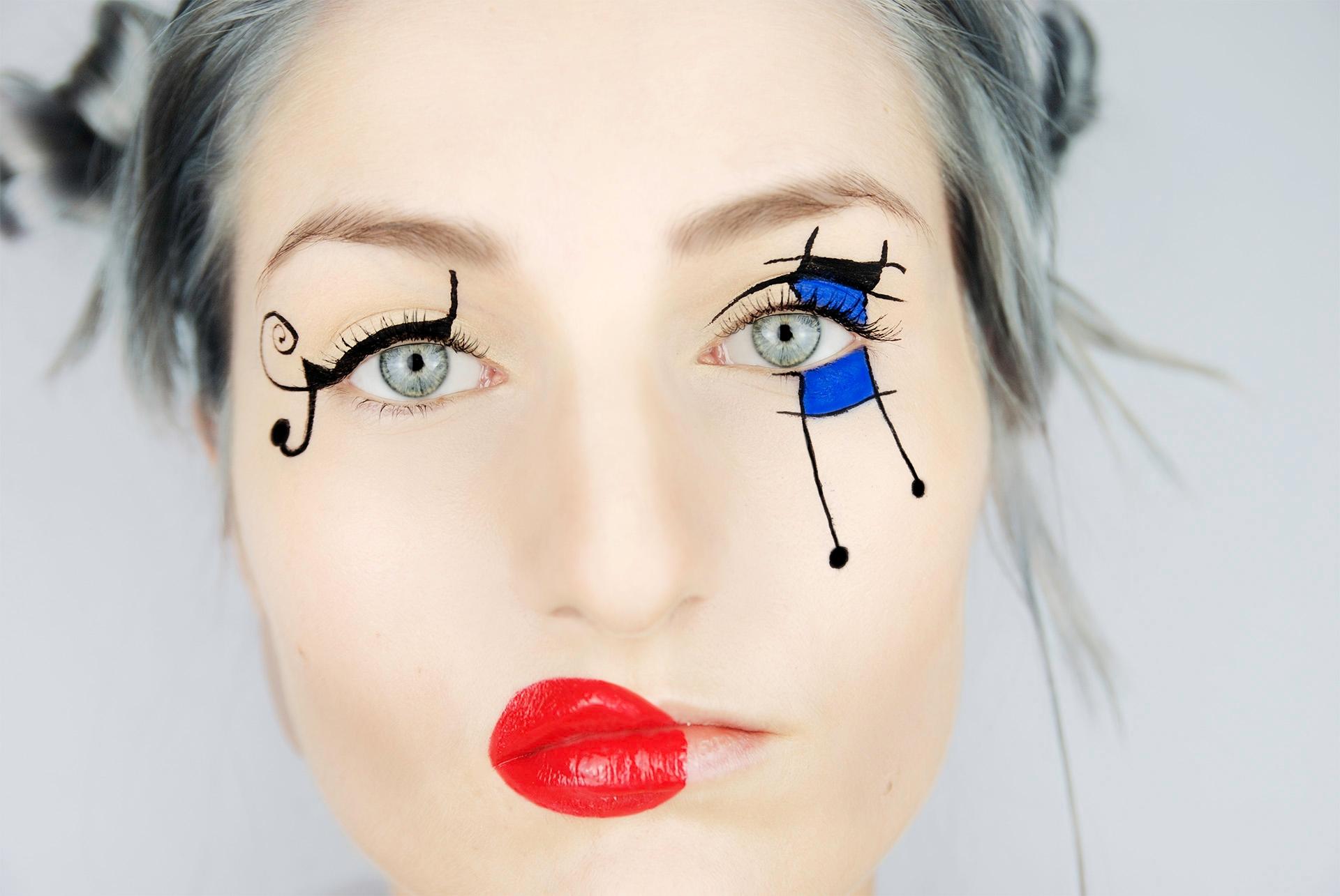 Zdjęcie przedstawia portret kobiety w artystycznym makijażu na szarym tle. Kobieta ma czerwone usta i niebiesko-czarne kształty na powiekach.