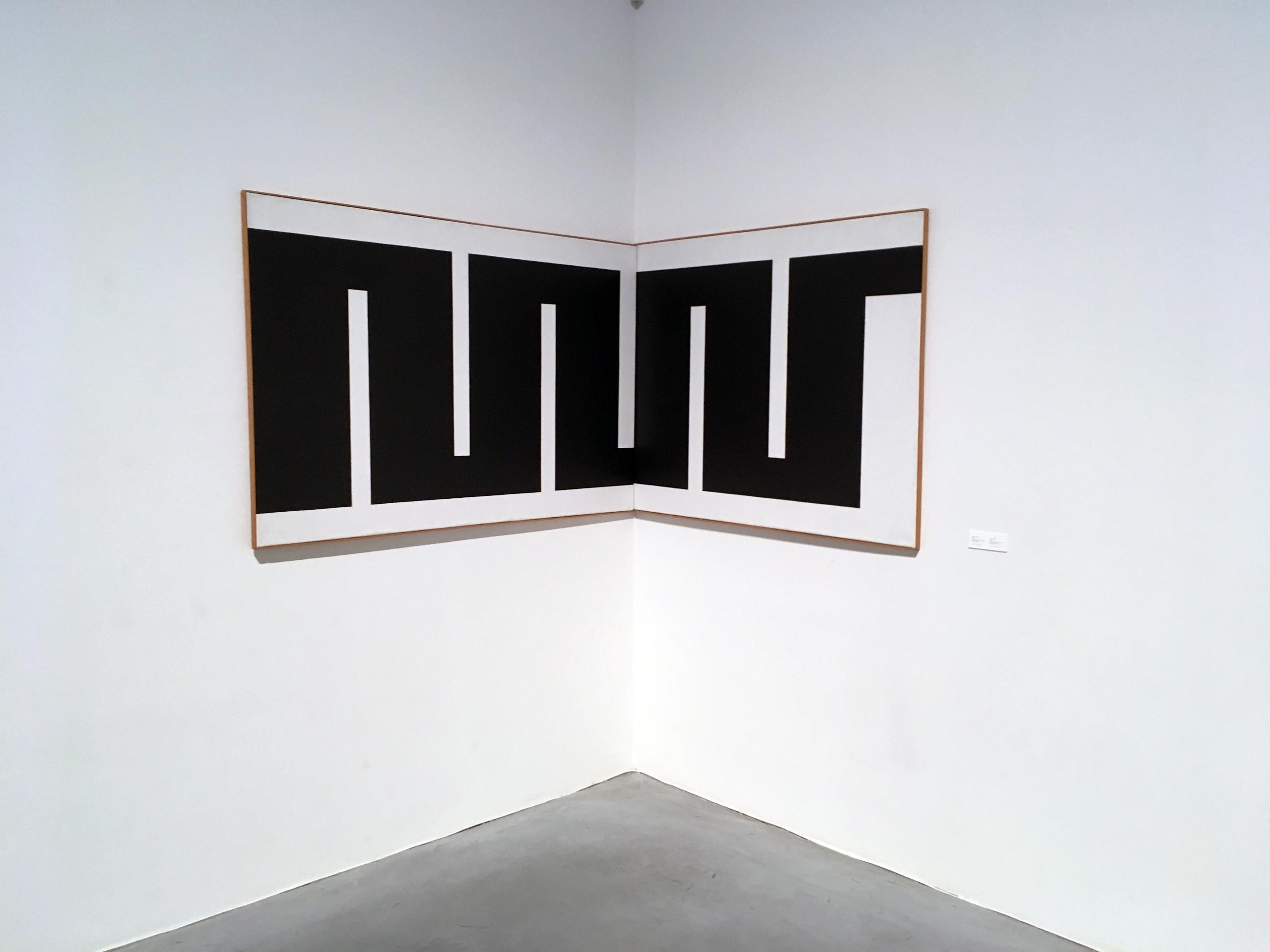 Zdjęcie przedstawia czarno-biały obraz zawieszony w rogu białej sali.