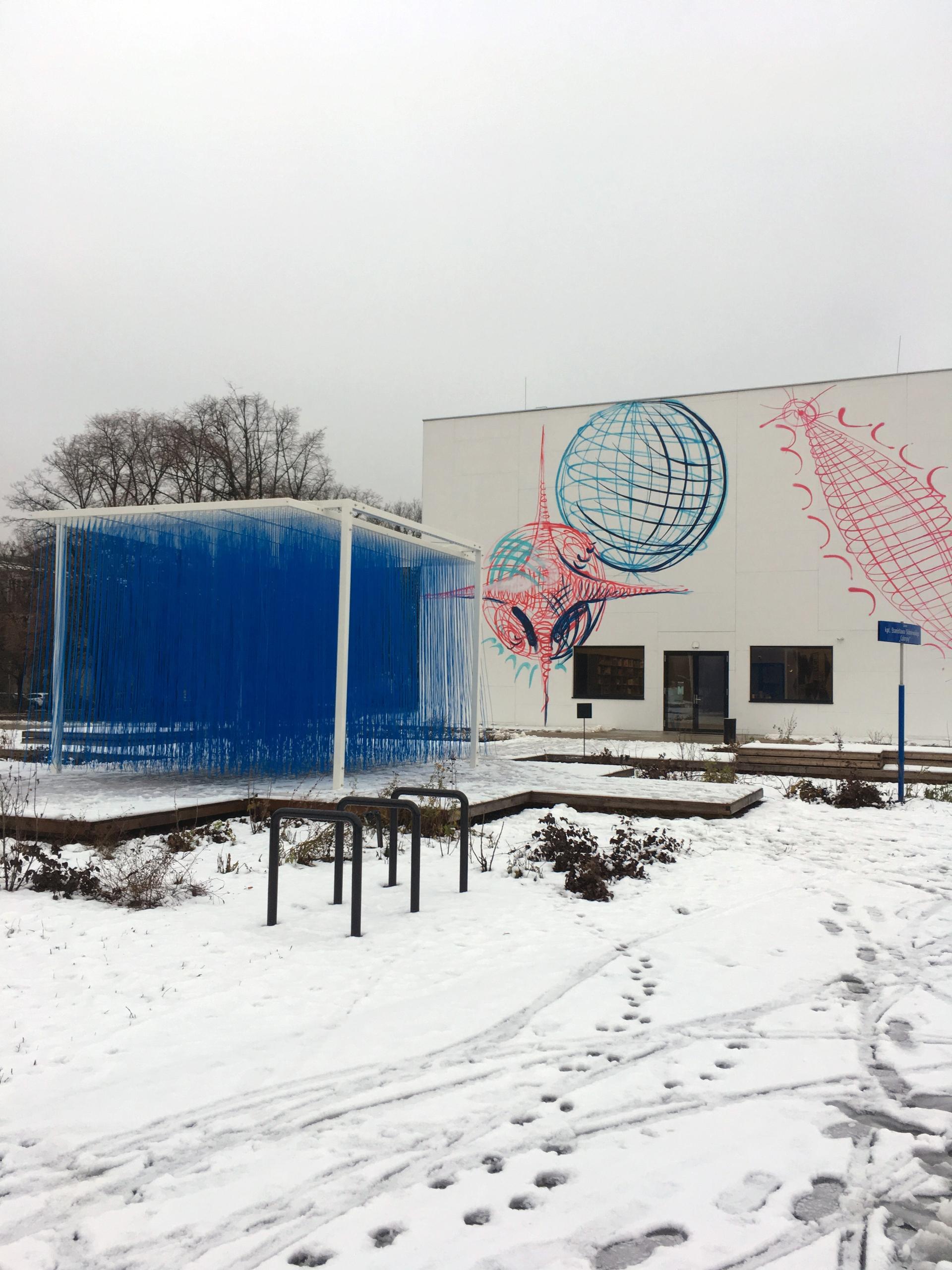 Zdjęcie przedstawia krajobraz. Widzimy biało-niebieską rzeźbę i budynek w tle. Ziemię pokrywa śnieg.