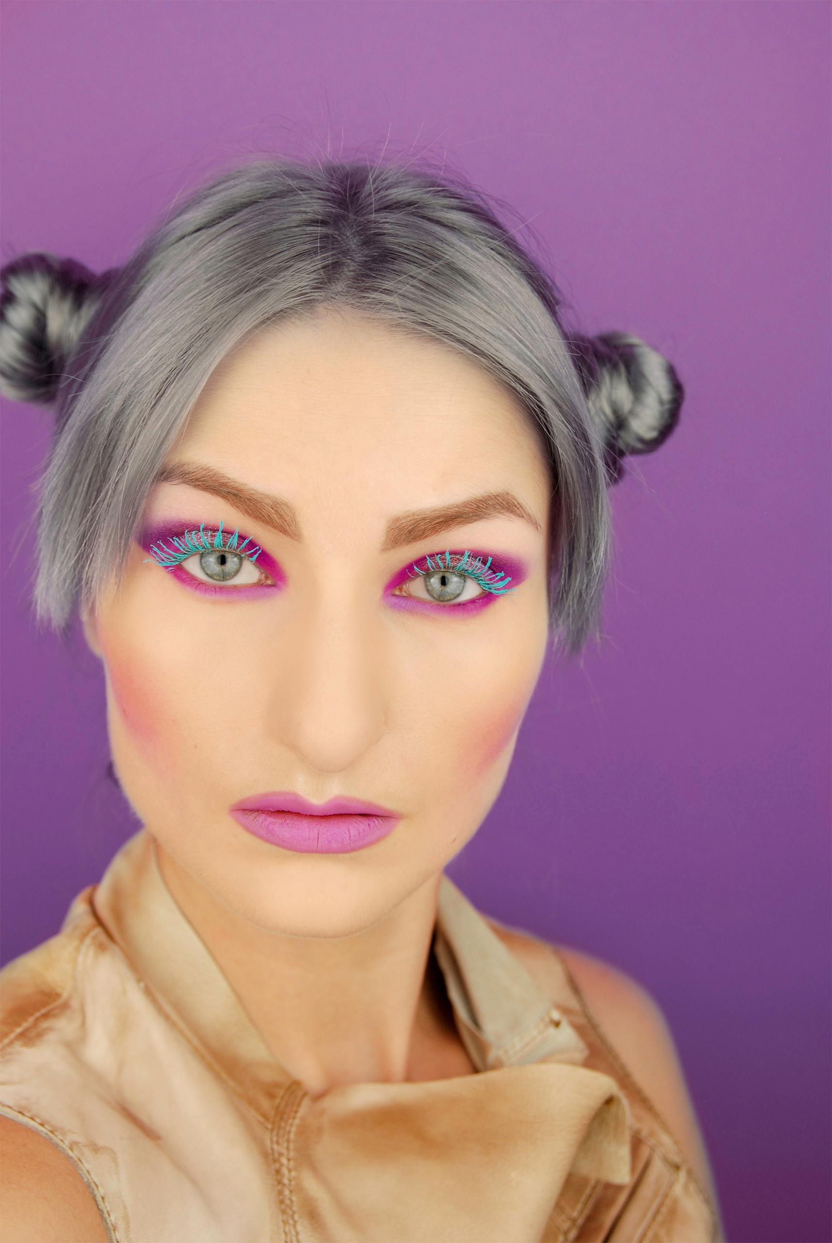 Zdjęcie przedstawia portret kobiety na fioletowym tle. Kobieta ma mocny makijaż i włosy siwego koloru.