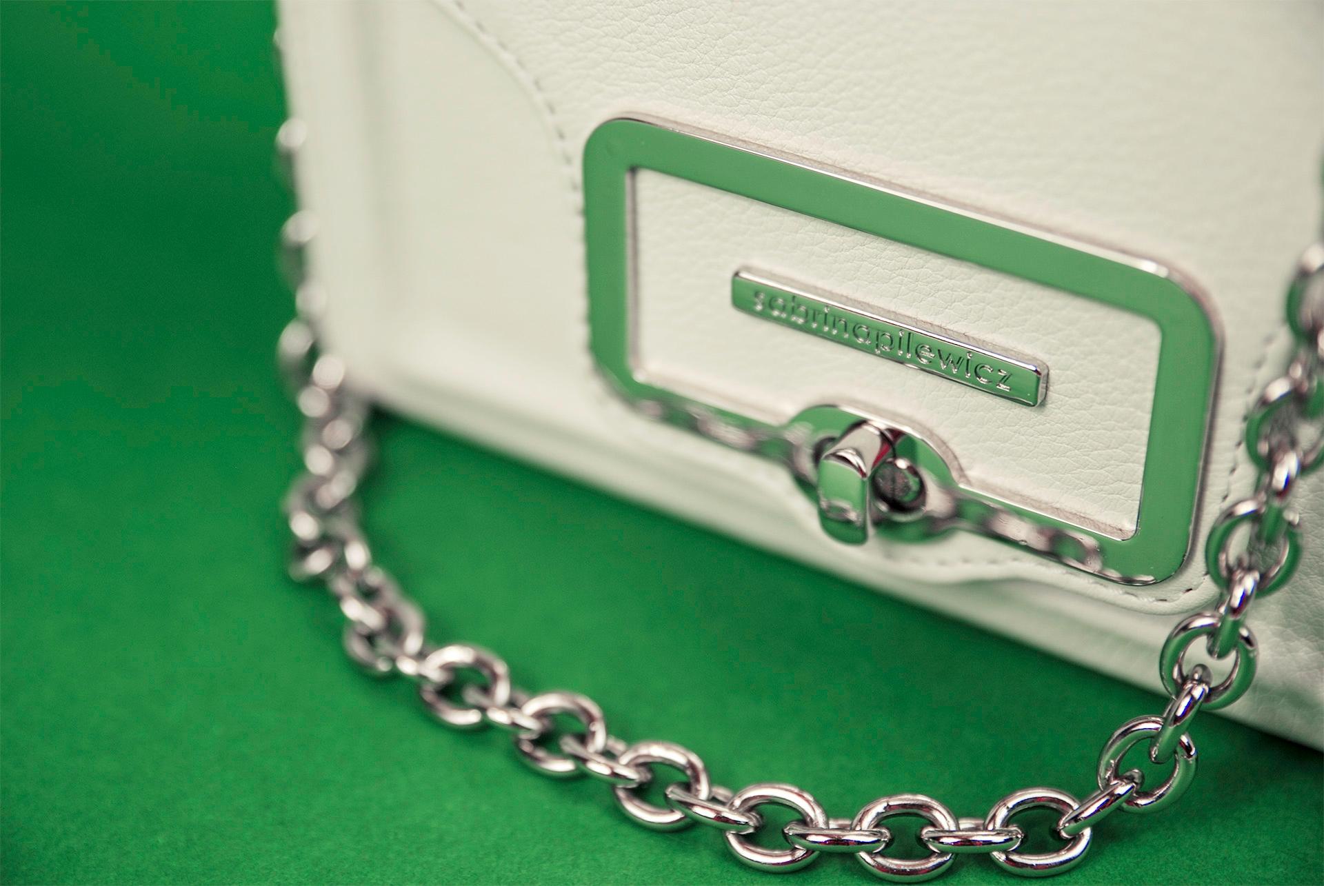 Zdjęcie przedstawia zbliżenie na fragment białej torebki ze srebrnym łańcuszkiem, która leży na zielonym podłożu.