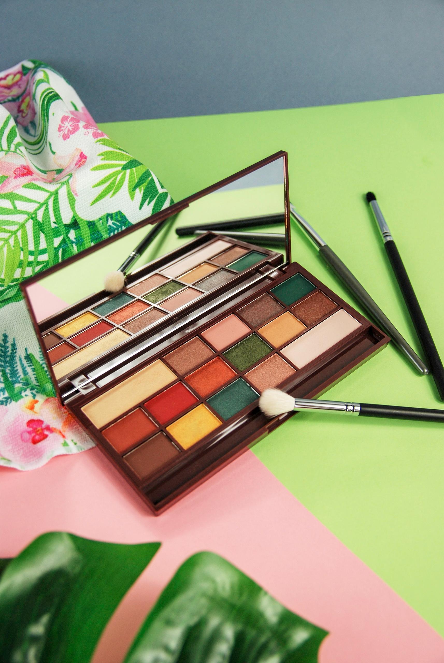 Zdjęcie przedstawia otwartą paletę z cieniami do makijażu oczu, obok leżą pędzle kosmetyczne, biała tkanina w kolorowe kwiaty, liść.