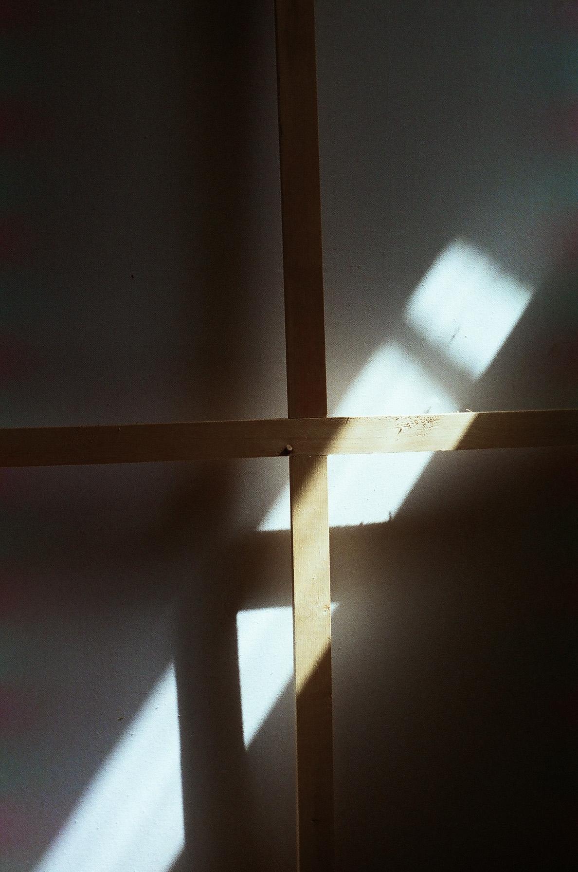 Zdjęcie przedstawia fragment obrazu, widzimy skrzyżowane deski i płótno oświetlone słonecznym światłem.