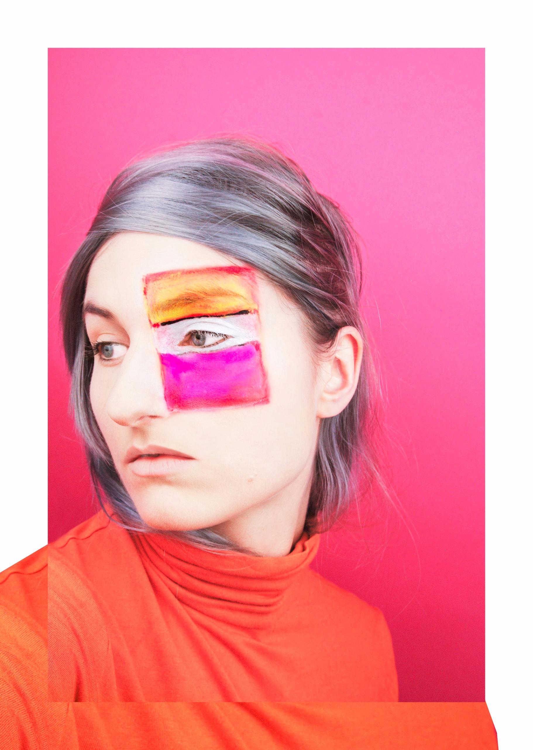 Zdjęcie przedstawia portret młodej kobiety z siwymi włosami na różowym tle. Kobieta ma na twarzy namalowany kolorowy prostokąt.