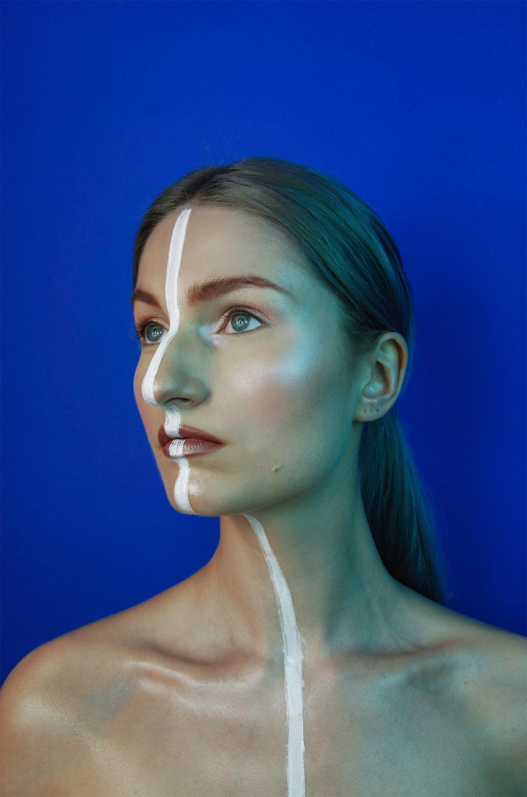 Zdjęcie przedstawia portret młodej kobiety. Przez środek jej twarzy biegnie pionowa biała linia. Całość na niebieskim tle.
