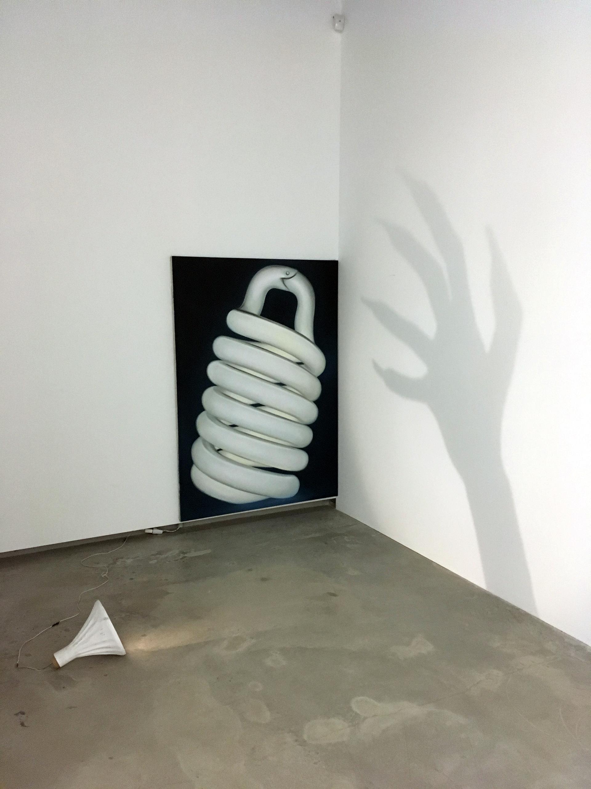 Zdjęcie przedstawia obraz, na którym namalowana jest gigantyczna żarówka, oraz lampkę leżącą na podłodze, która rzuca cień w kształcie ręki.