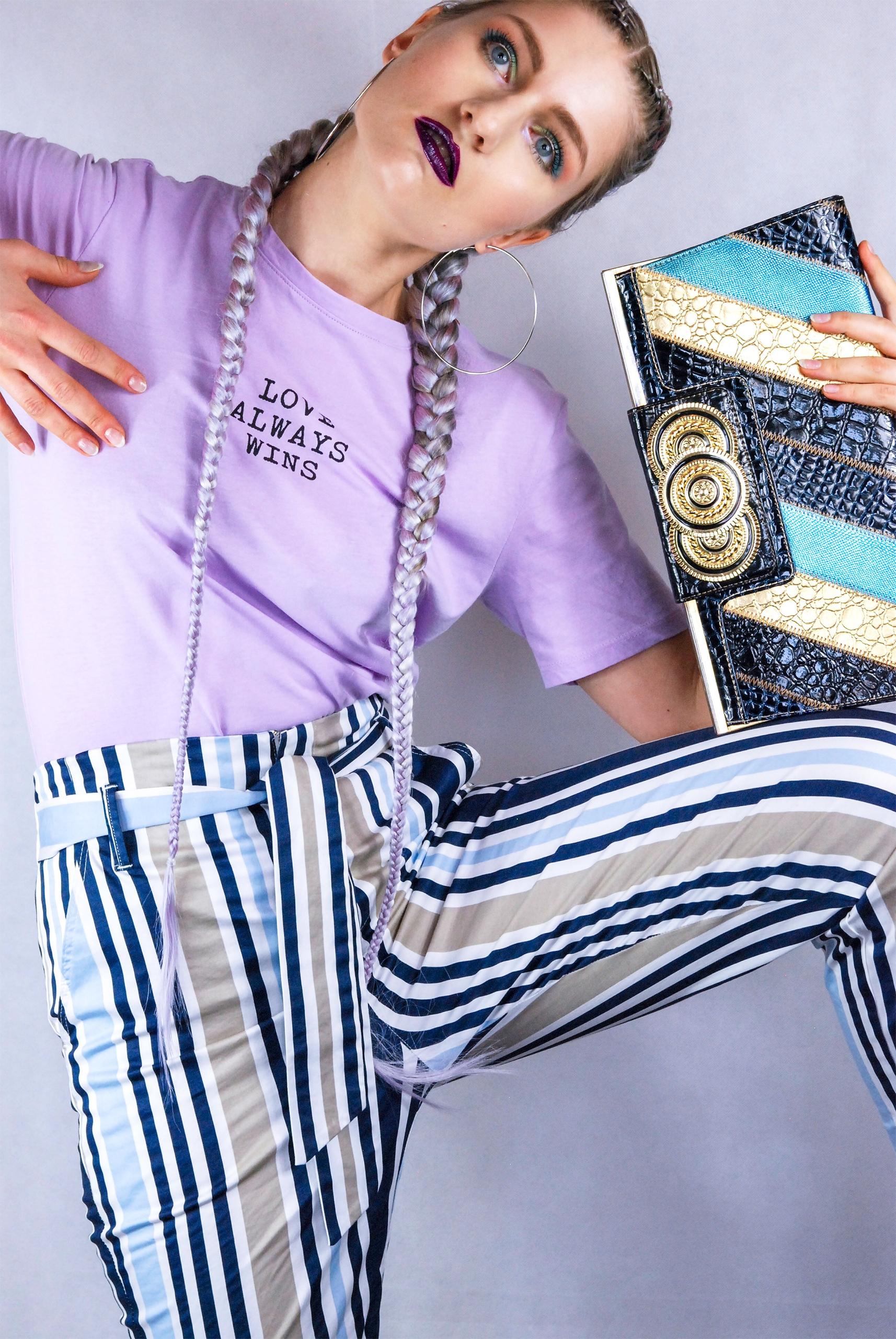 Zdjęcie przedstawia kobietę w nienaturalnej pozie. Kobieta ma na sobie spodnie w paski i jasno-fioletową koszulkę.