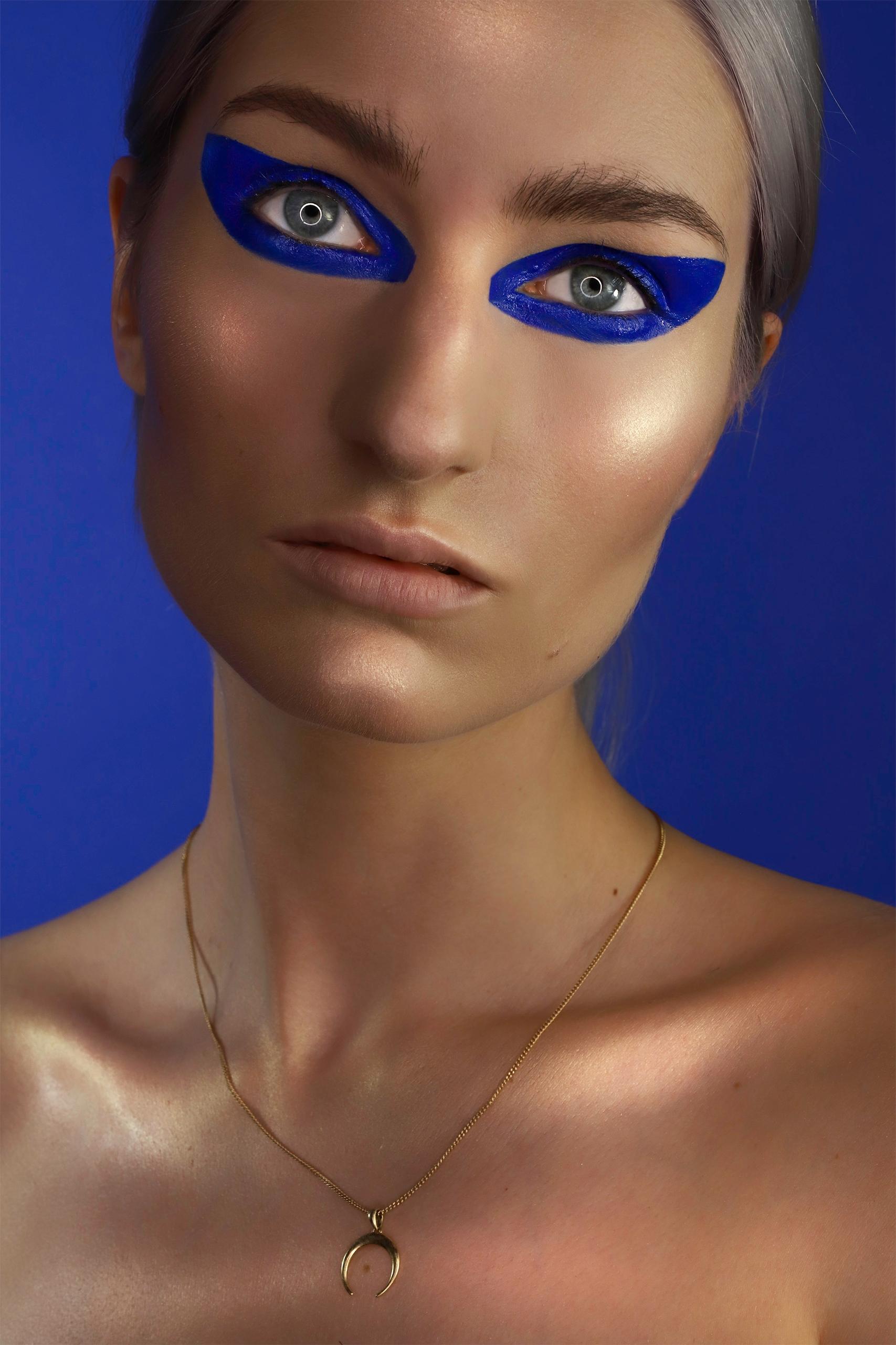 Zdjęcie przedstawia portret kobiety w mocnym makijażu na granatowym tle.