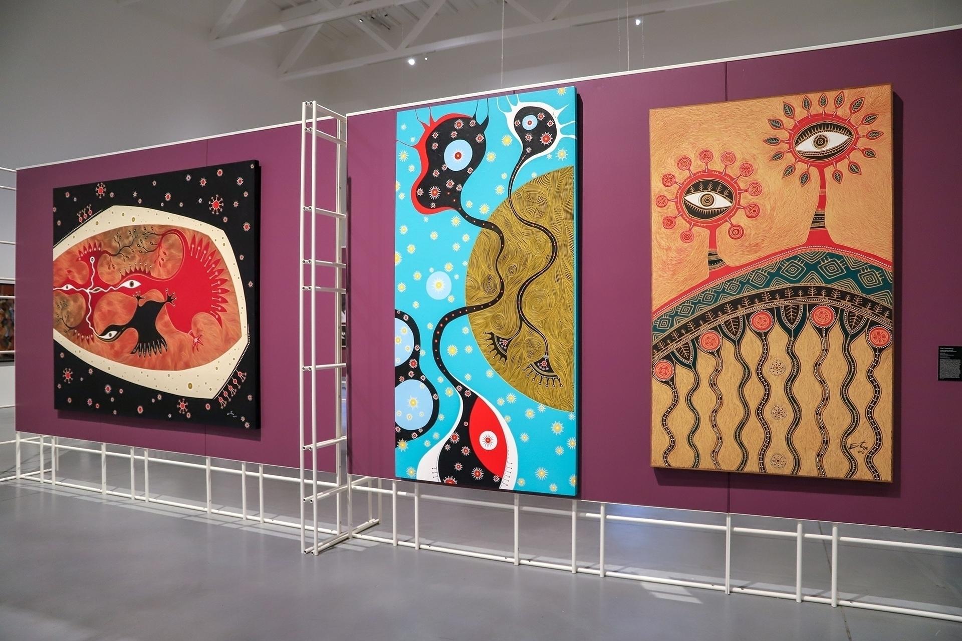 Zdjęcie przedstawia przestrzeń ekspozycji muzealnej z trzema kolorowymi obrazami na pierwszym planie.