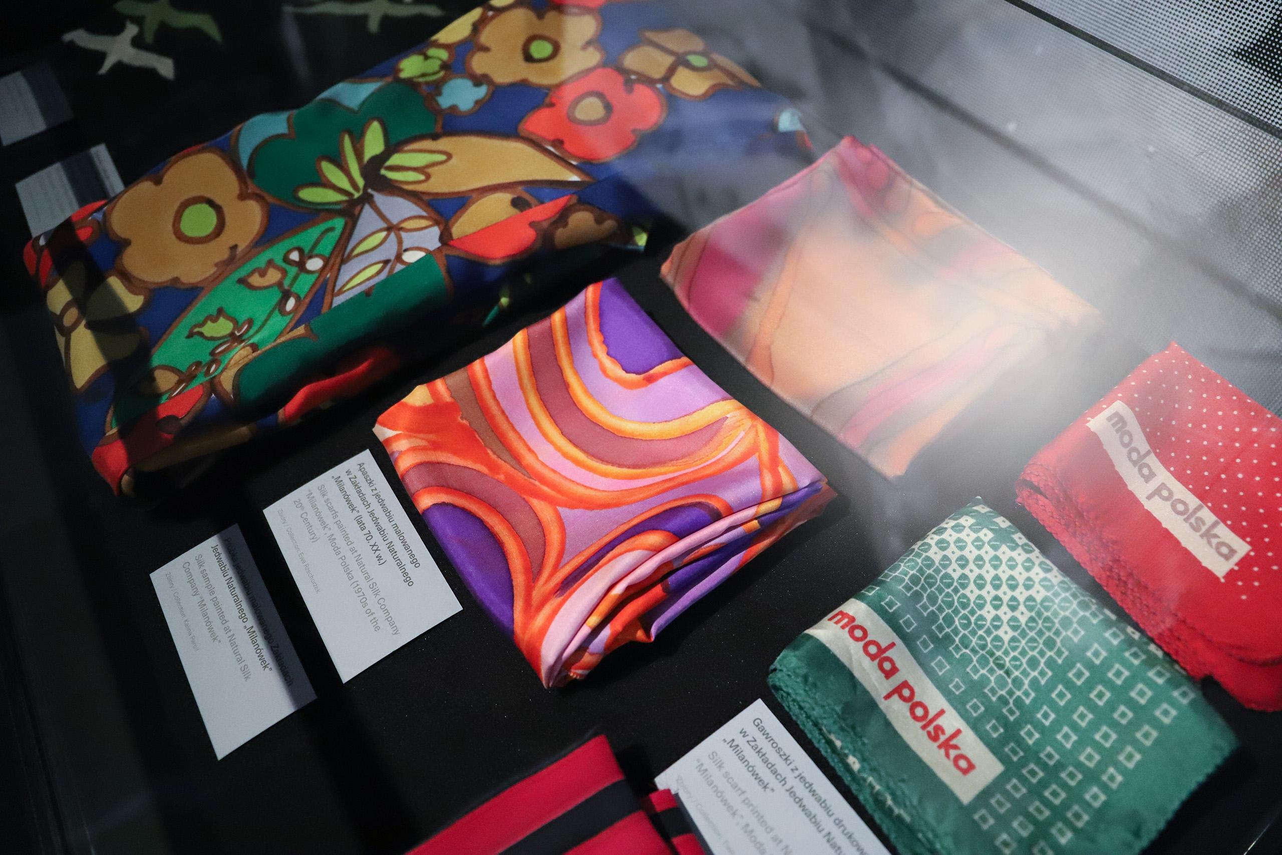 Zdjęcie przedstawia kolorowe materiały ułożone na stole, zamknięte w szklanej gablocie.