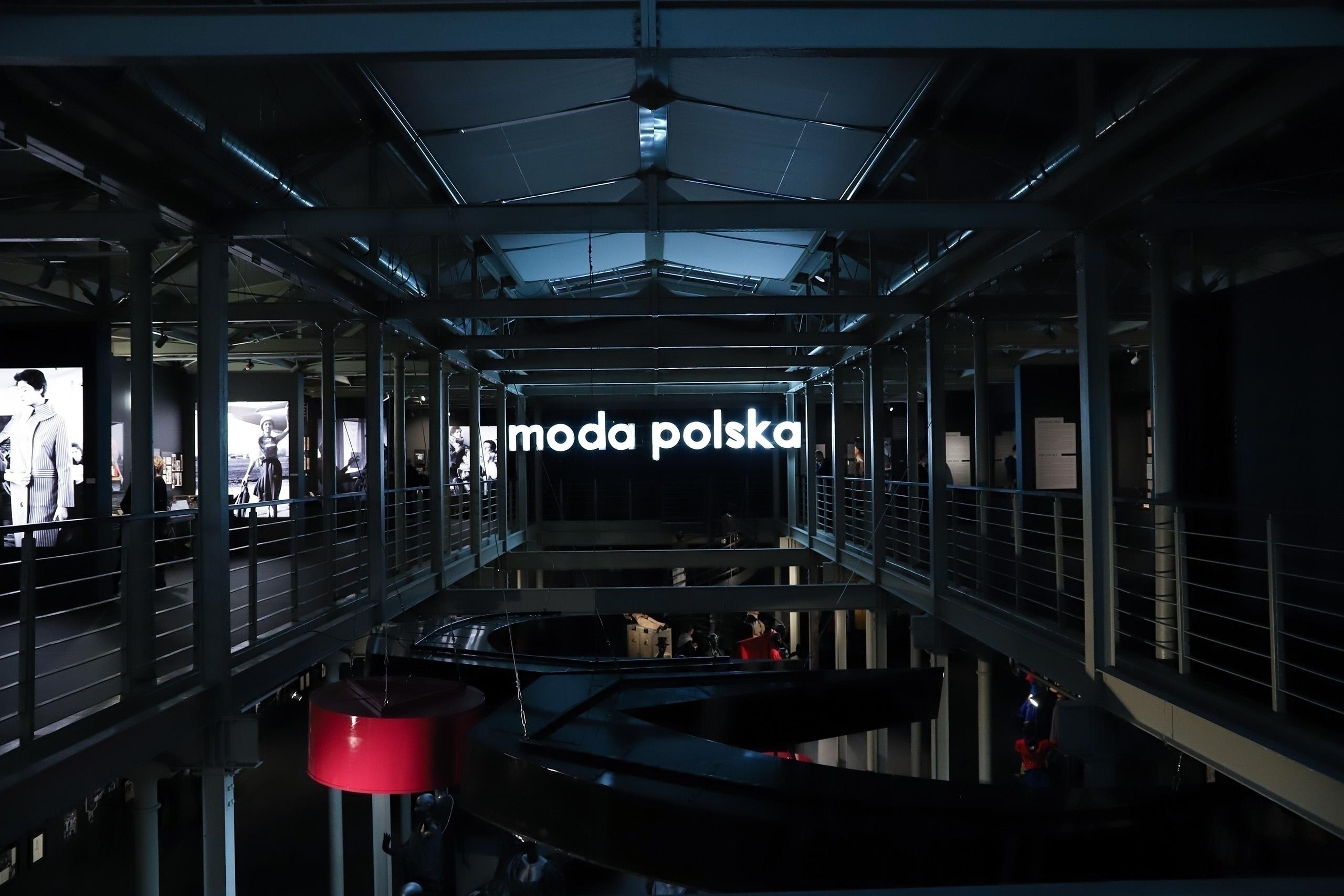 Zdjęcie przedstawia ciemne pomieszczenie, które oświetla jedynie biały neon z napisem.