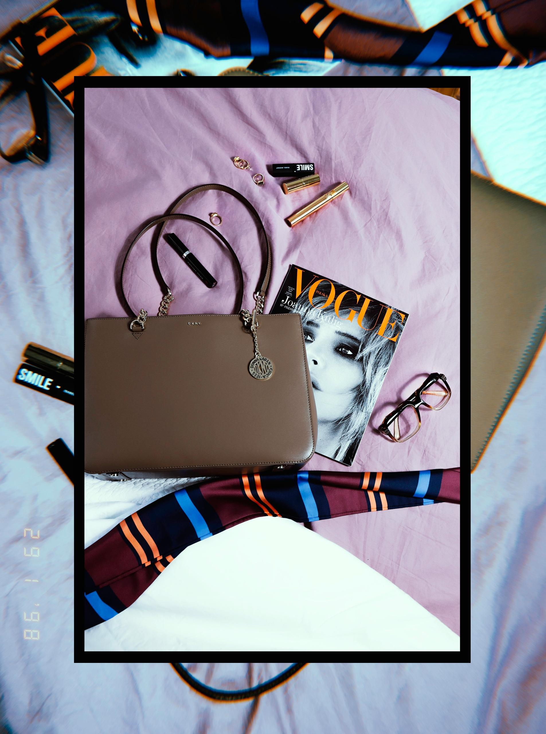 Obraz przedstawia fotografię torebki leżącej na fioletowej tkaninie wśród różnych przedmiotów.