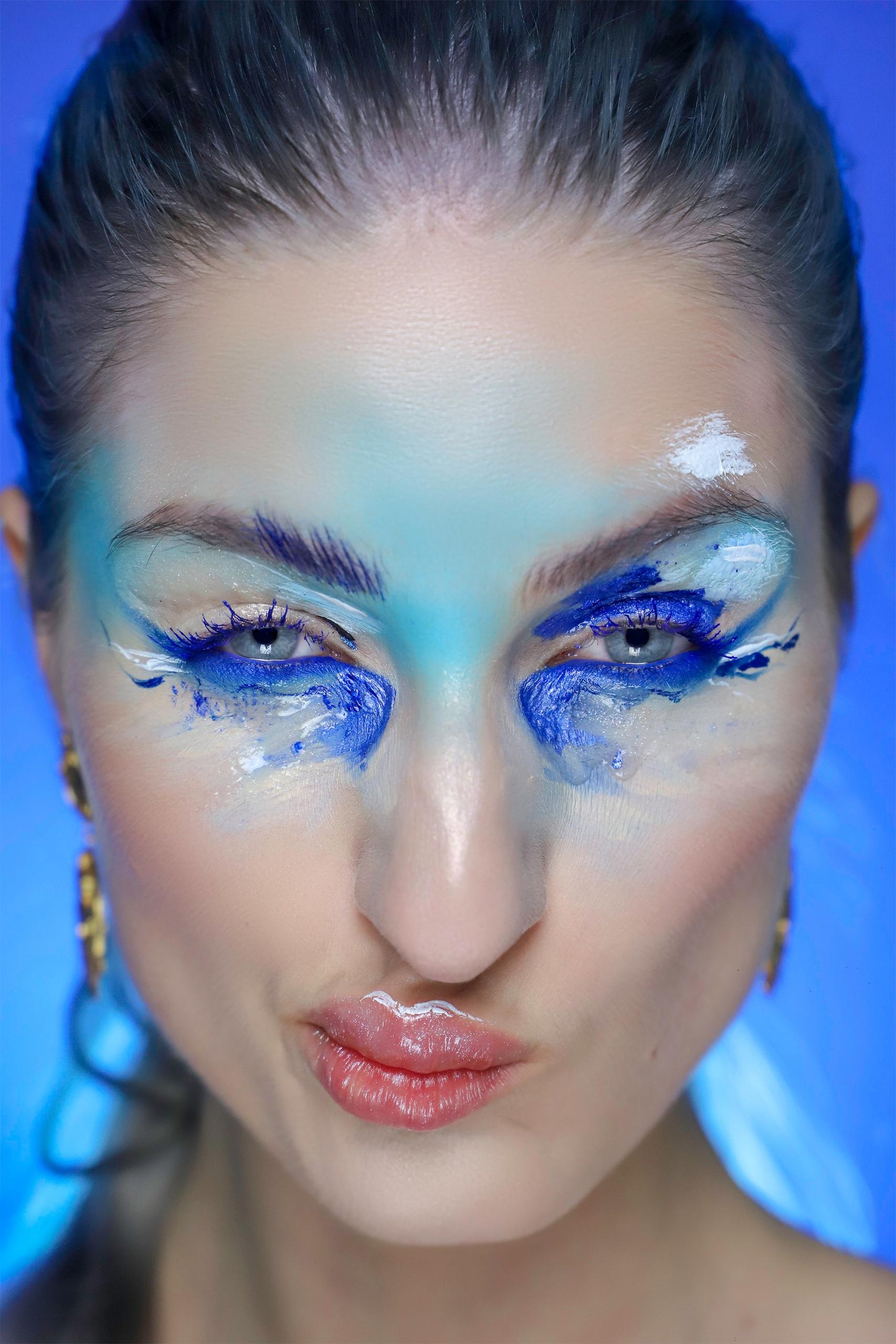 Fotografia przedstawia twarz kobiety w artystycznym makijażu. Kobieta ma skrzywioną minę. Całość na niebieskim tle.
