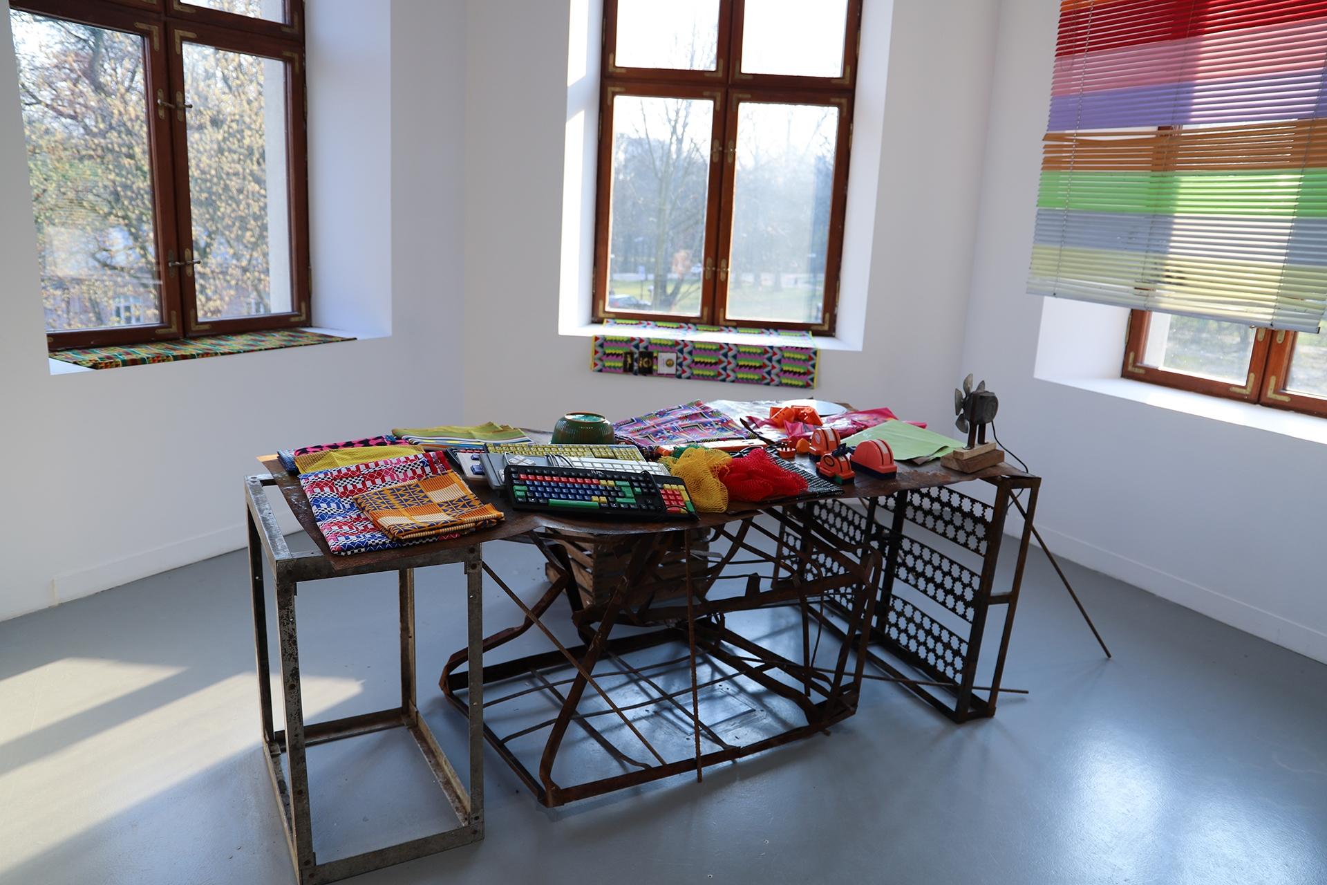 Fotografia przedstawia pomieszczenie, na środku którego stoi stolik z różnymi przedmiotami.