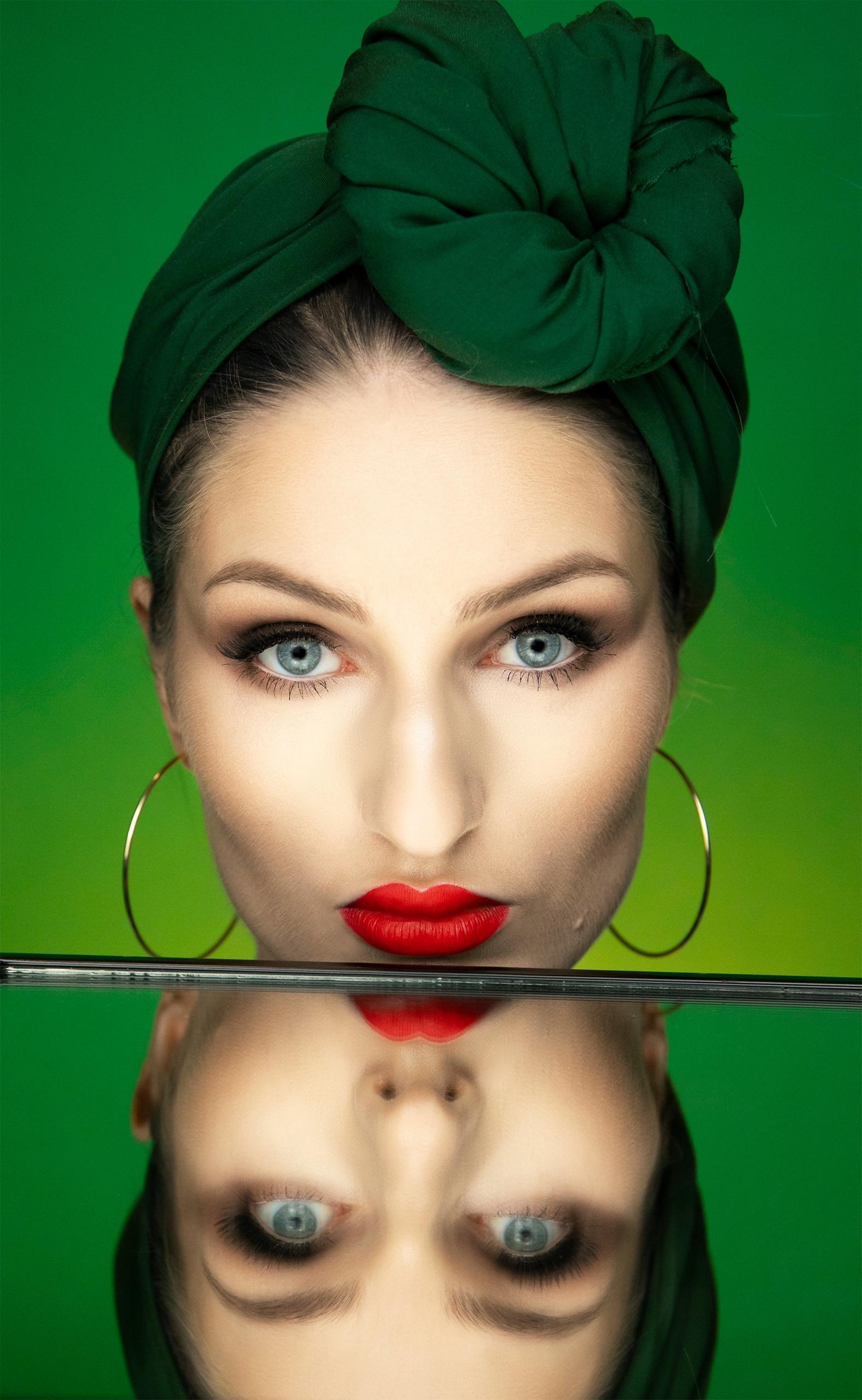 Zdjęcie przedstawia portret kobiety w zielonej chustce na głowie. Kobieca twarz z czerwonymi ustami odbija się w lustrze.