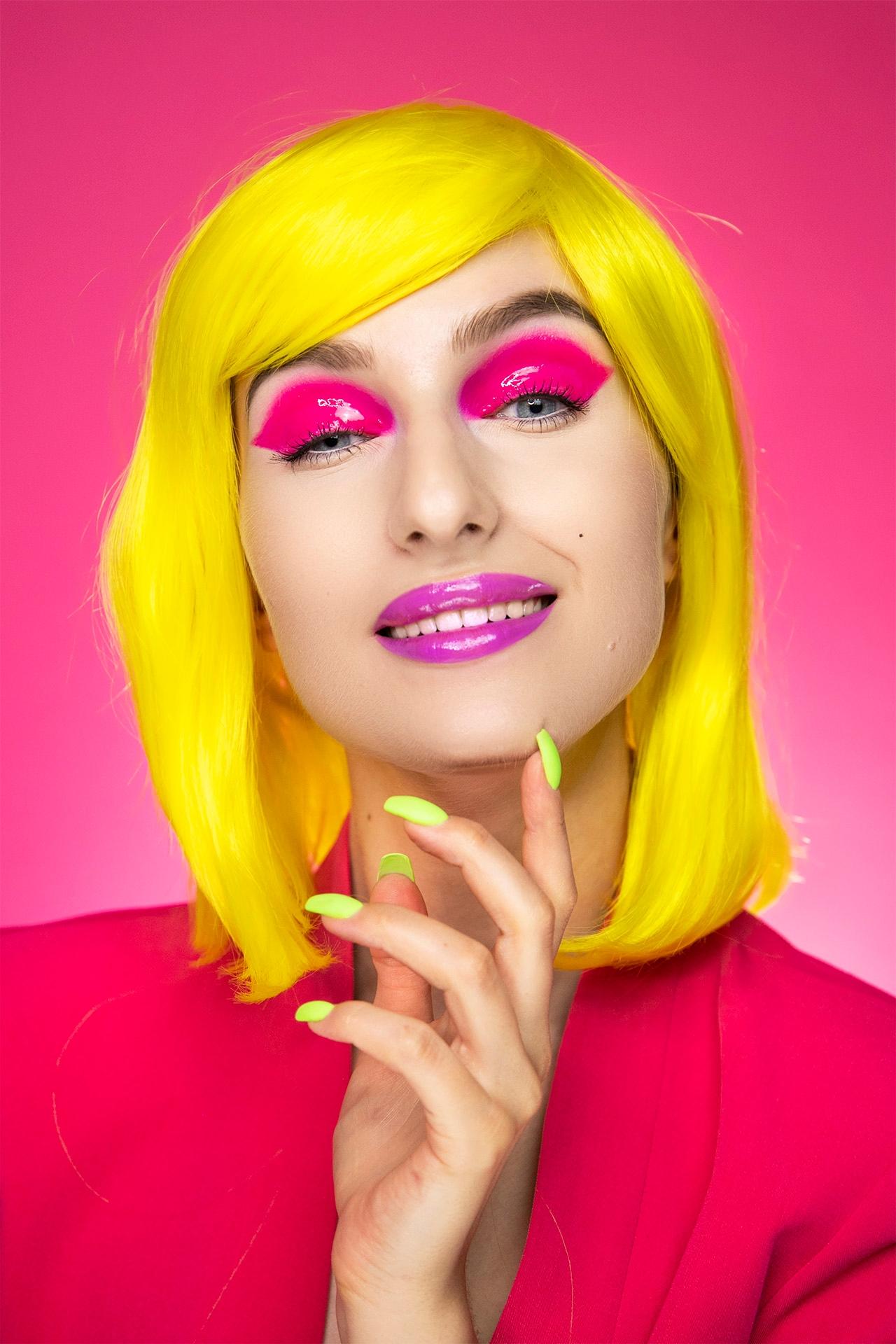 Zdjęcie przedstawia uśmiechniętą kobietę w żółtych włosach. Kobieta ma powieki pomalowane na różowo i opiera podbródek o lewą dłoń.