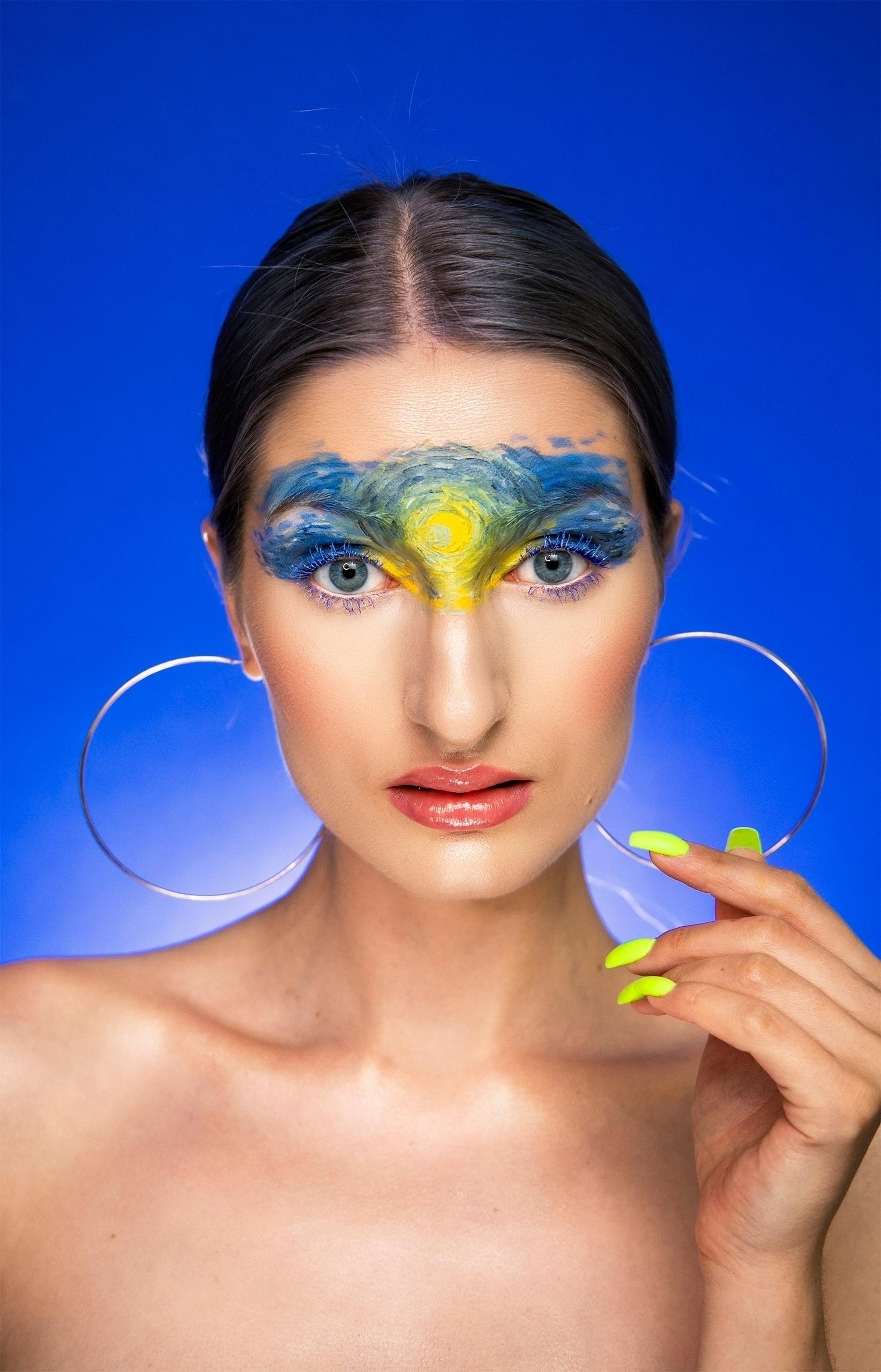 Fotografia przedstawia kobietę na niebieskim tle w mocnym makijażu. Kobieta ma na sobie kolczyki w kształcie kół.